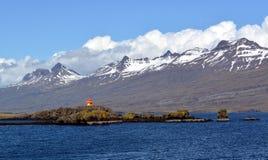 以东部海湾的玄武岩山的多雪的山峰的为背景一座灯塔在冰岛 库存照片