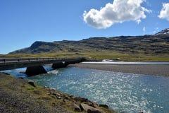 以东部海湾的玄武岩山的多雪的山峰的为背景一座灯塔在冰岛 免版税库存图片
