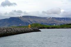 以东部海湾的玄武岩山的多雪的山峰的为背景一座灯塔在冰岛 免版税库存照片