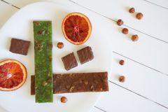 东部纤巧churchkhela、榛子、红色橙色一半和一个巧克力块被绘的委员会白色表面上  ?? 免版税库存图片