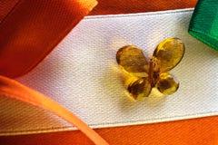 丝带在一只装饰蝴蝶由玻璃制成的中心,家庭装饰的织品零件用他们自己的手 免版税库存照片