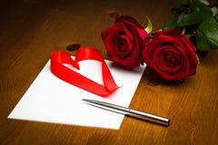 丝带在纸的爱心脏与笔和玫瑰 图库摄影