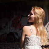 丝毫透亮女衬衫的孤独的blondy妇女在被放弃的大厦 图库摄影