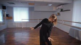 丝绸黑衣服跳舞的美丽的白发舞蹈家在有芭蕾纬向条花和镜子的教室在墙壁上 教师 股票录像