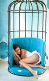 丢失在熟睡 疲乏的女孩白天睡眠笼子椅子的 在铁栅栏的妇女睡眠 甜舒适梦想,早晨 免版税库存图片