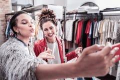 两一起做selfie的愉快的放光的shopaholics在买衣裳以后 库存图片