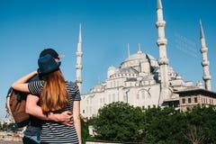 两三个游人一个年轻人和一名俏丽的妇女一起拥抱并且也看举世闻名的蓝色清真寺 库存照片