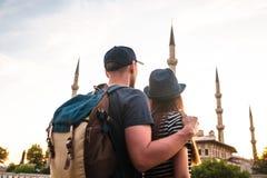两三个游人一个年轻人和一名俏丽的妇女一起拥抱并且也看举世闻名的蓝色清真寺 免版税库存照片