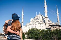 两三个游人一个年轻人和一名俏丽的妇女一起拥抱并且也看举世闻名的蓝色清真寺 免版税图库摄影