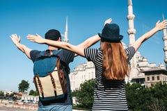 两三个游人一个年轻人和一名俏丽的妇女在举世闻名的蓝色清真寺旁边在伊斯坦布尔举了他们的手 免版税库存图片