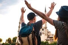 两三个游人一个年轻人和一名俏丽的妇女在举世闻名的蓝色清真寺旁边在伊斯坦布尔举了他们的手 库存图片