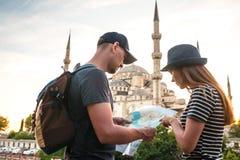 两三个游人一个年轻人和一名俏丽的妇女看地图在举世闻名的蓝色清真寺旁边也叫 免版税库存照片