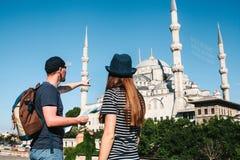 两三个游人一个年轻人和一名俏丽的妇女看地图在举世闻名的蓝色清真寺旁边也叫 库存图片