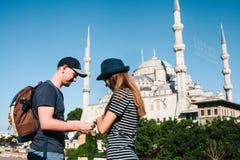两三个游人一个年轻人和一名俏丽的妇女看地图在举世闻名的蓝色清真寺旁边也叫 免版税图库摄影