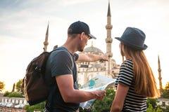 两三个游人一个年轻人和一名俏丽的妇女看地图在举世闻名的蓝色清真寺旁边也叫 免版税库存图片