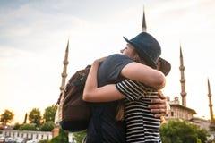 两三个游人一个年轻人和一名美丽的妇女拥抱反对举世闻名的蓝色清真寺,也叫 库存照片