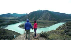 两三个游人来临在它上面一座石山,一条快速的山河下面流动 回到视图 股票录像