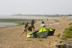 两三个年轻人努力反对强风他们的巴拉滑翔机为下午体育做准备在海滩 图库摄影