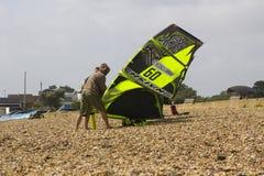 两三个年轻人努力反对强风他们的巴拉滑翔机为下午体育做准备在Titchfield海滩 免版税库存图片