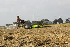 两三个年轻人努力反对强风他们的巴拉滑翔机为下午体育做准备在Titchfield海滩 图库摄影