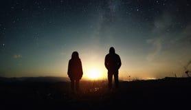 两三人民男人和妇女站立在月亮的日落在与明亮的星和银河的满天星斗的天空下 免版税库存照片