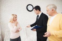两三位老人咨询律师 律师拿着纸的一个黑文件夹 免版税库存图片