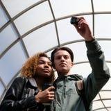 两三名学生被拍摄在玻璃圆顶里面 有一块黑玻璃的一个美丽的非裔美国人的女孩和欧洲人 库存照片