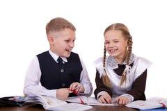 两三名小学学生坐在书桌 免版税库存图片
