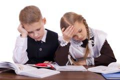 两三名小学学生坐在书桌 图库摄影