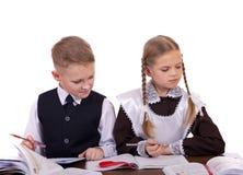 两三名小学学生坐在书桌 库存图片