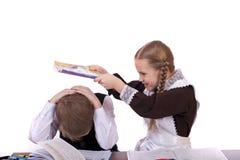 两三名小学学生坐在书桌 免版税图库摄影