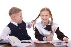 两三名小学学生坐在书桌 库存照片