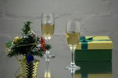两三块玻璃用在一张白色木桌上的金香槟与与云杉小树枝的圣诞节球在红色背景的 库存照片
