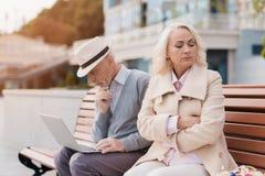 两三退休的人坐在购物中心的一条长凳 一个人研究膝上型计算机,妇女被触犯在他 免版税库存照片