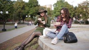 两不同和异常的妇女在街道三明治和油炸物吃 影视素材