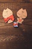 两与一把红色弓的木猫 免版税库存照片