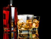 两与冰的威士忌酒在玻璃临近在黑背景的瓶 免版税库存图片