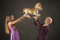 两与古色古香的转盘马的少妇跳舞 免版税库存照片