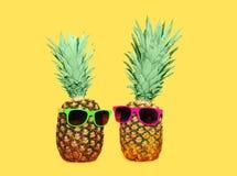 两与太阳镜的菠萝在黄色背景,五颜六色的凤梨 免版税库存照片