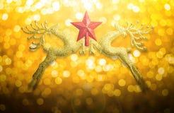 两与红色星的金黄驯鹿在圆bokeh金银铜合金背景和拷贝空间 免版税库存图片