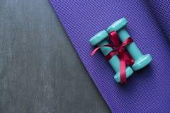 两与红色礼物弓的绿色哑铃在瑜伽席子背景 免版税图库摄影
