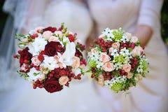 两与红色花的美丽的婚礼花束 库存照片