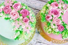 两与花的庆祝的蛋糕在白色木背景上升了 库存图片