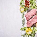 两与菜的猪肉牛排在切板加香料草本边界,地方文本木土气背景名列前茅vi 免版税库存图片