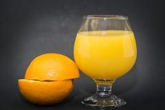 两个一半看法桔子和酒杯用金黄开胃汁液 库存照片