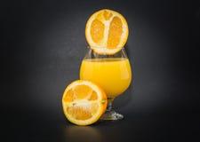 两个一半看法桔子和酒杯用金黄开胃汁液 图库摄影