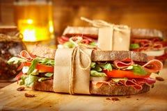 两个三明治用烟肉和新鲜蔬菜在木的葡萄酒 免版税库存照片