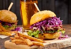 两个三明治用被拉扯的猪肉、炸薯条和杯在木背景的啤酒 图库摄影