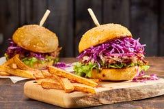 两个三明治用被拉扯的猪肉、炸薯条和杯在木背景的啤酒 库存图片