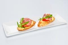 两个三明治用serrano火腿、乳酪和芝麻菜在板材 免版税库存照片